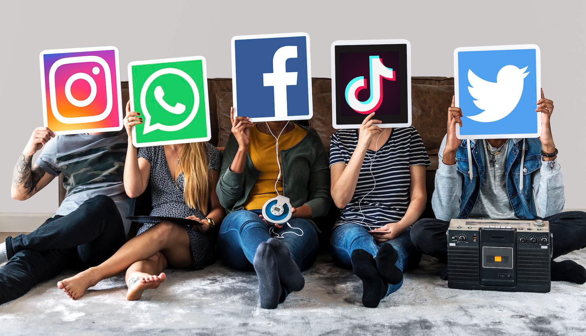 Ragazzi tengono in mano dei cartelli con i loghi dei social network
